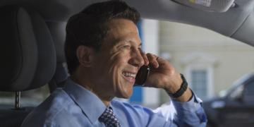 05 Oct 2012 --- Hispanic businessman talking on his cellphone in his car --- Image by © Steve Prezant/Corbis